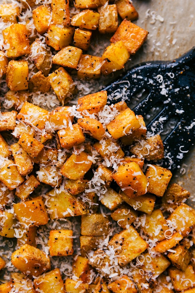 Overhead image of Roasted Potatoes with a spatula picking some up.