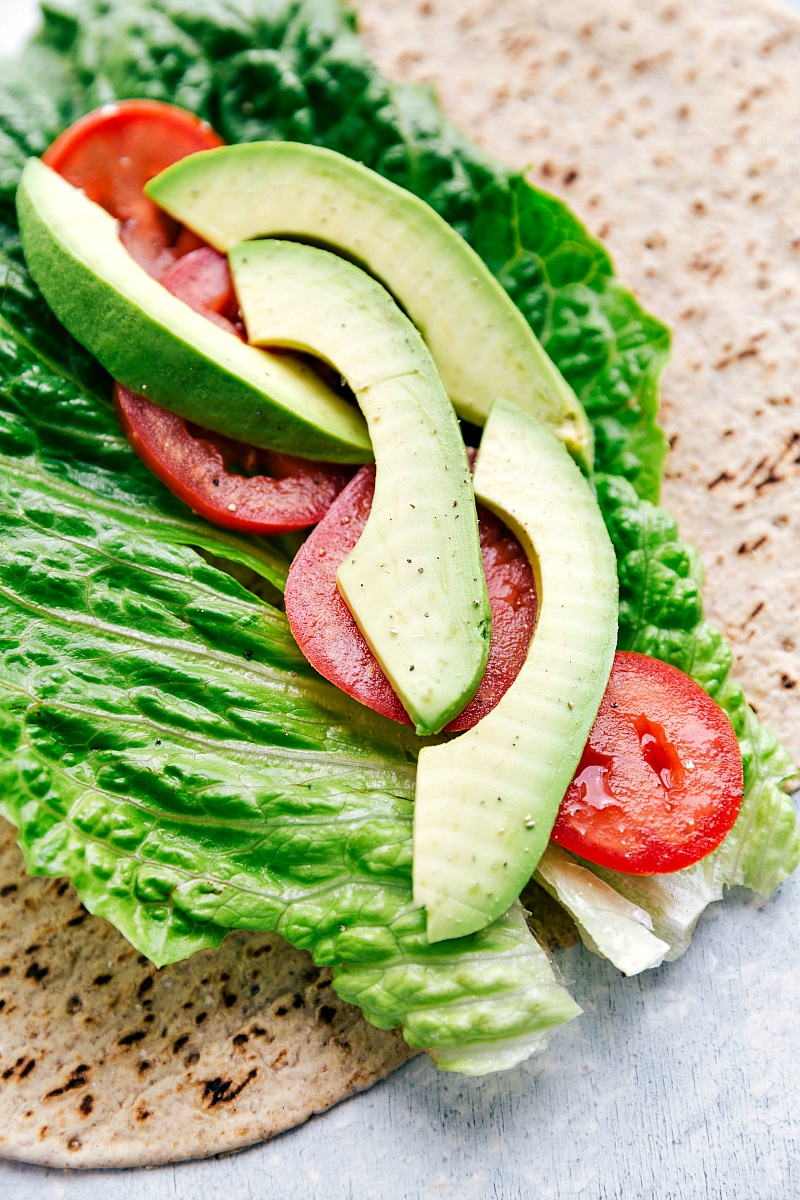 Image of the wrap open with lettuce, tomatoes, and avocado on it for these chicken salad wrap