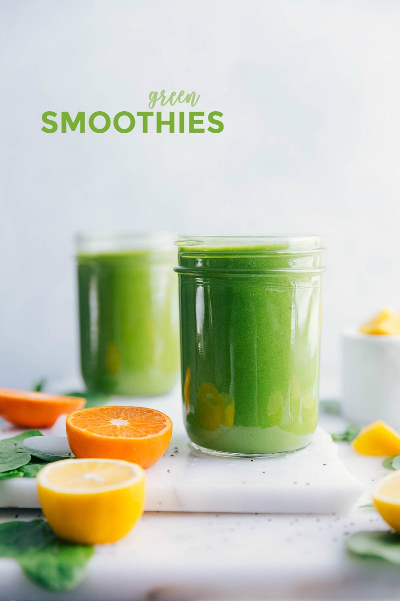 Green smoothie recipe: 2 glasses on a table with citrus surrounding it