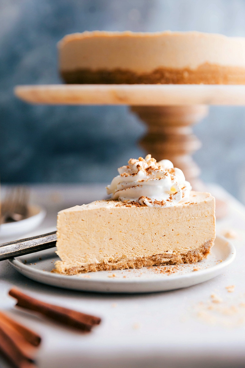 Image of a slice of No-Bake Pumpkin Cheesecake with the whole cheesecake in the background.