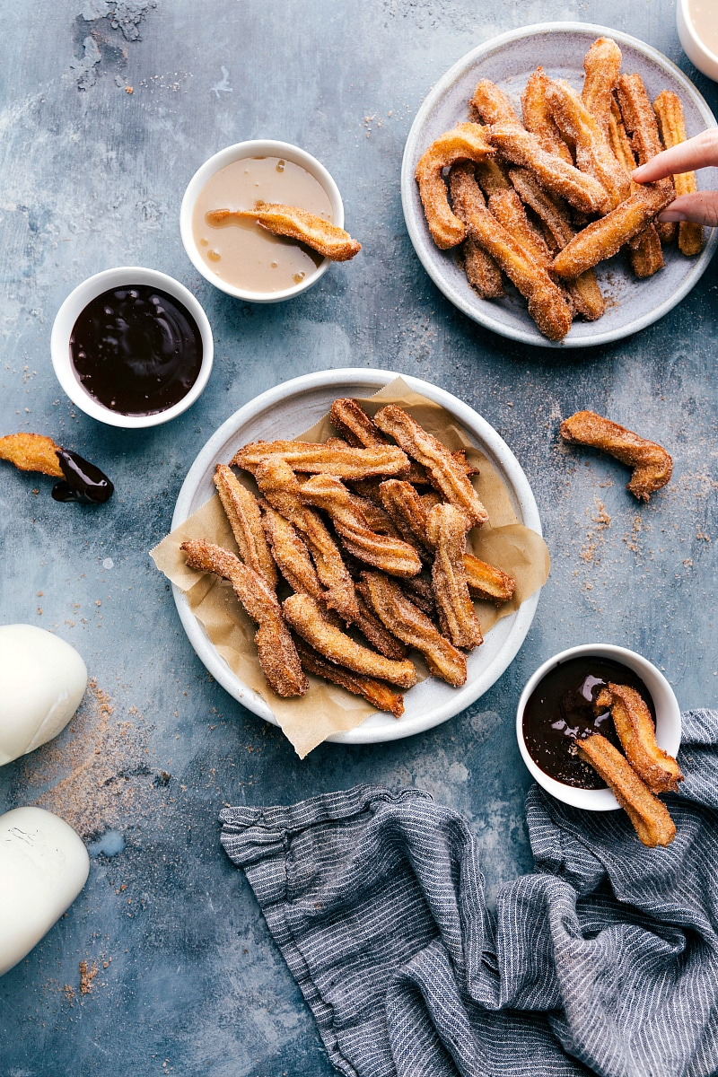 Overhead image of a plate of Churros and dipping sauces on the side