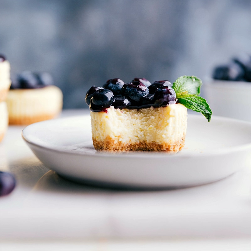 Image of one Mini Blueberry Cheesecake with a bite taken out of it.