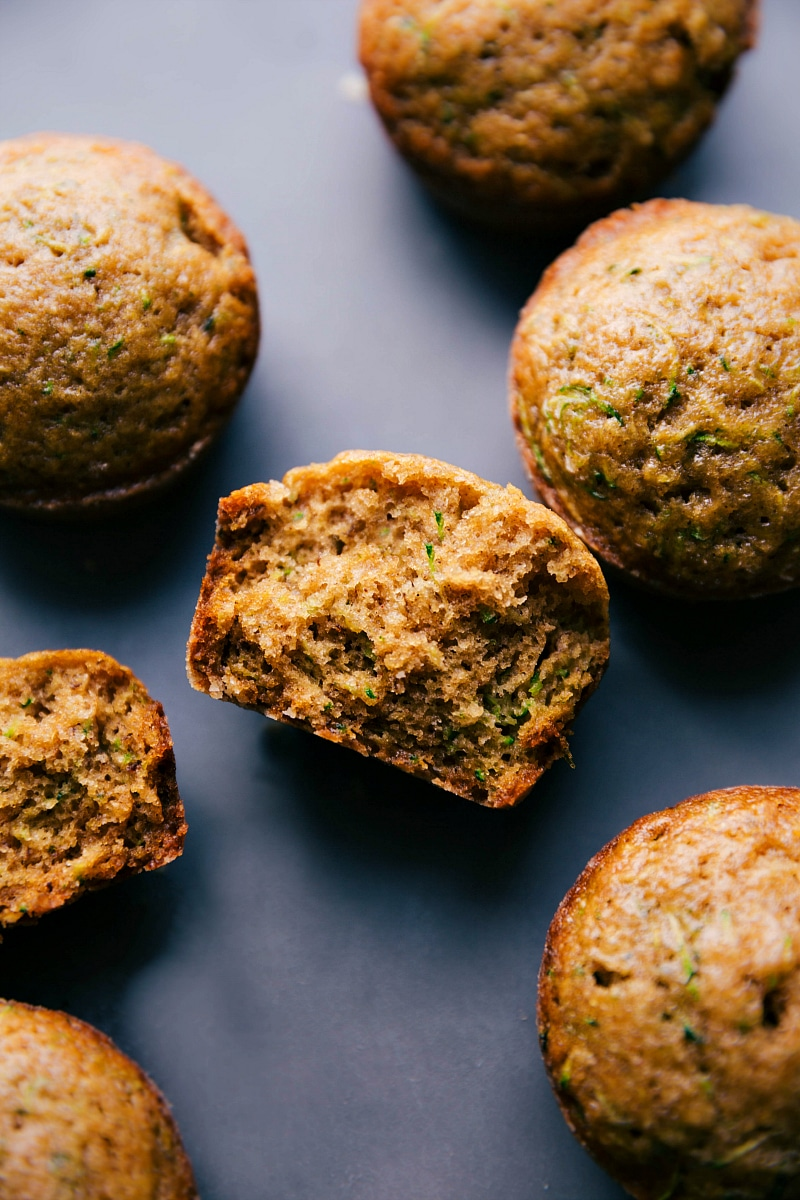 View of Healthy Zucchini Muffins, with one split in half to show the inside.
