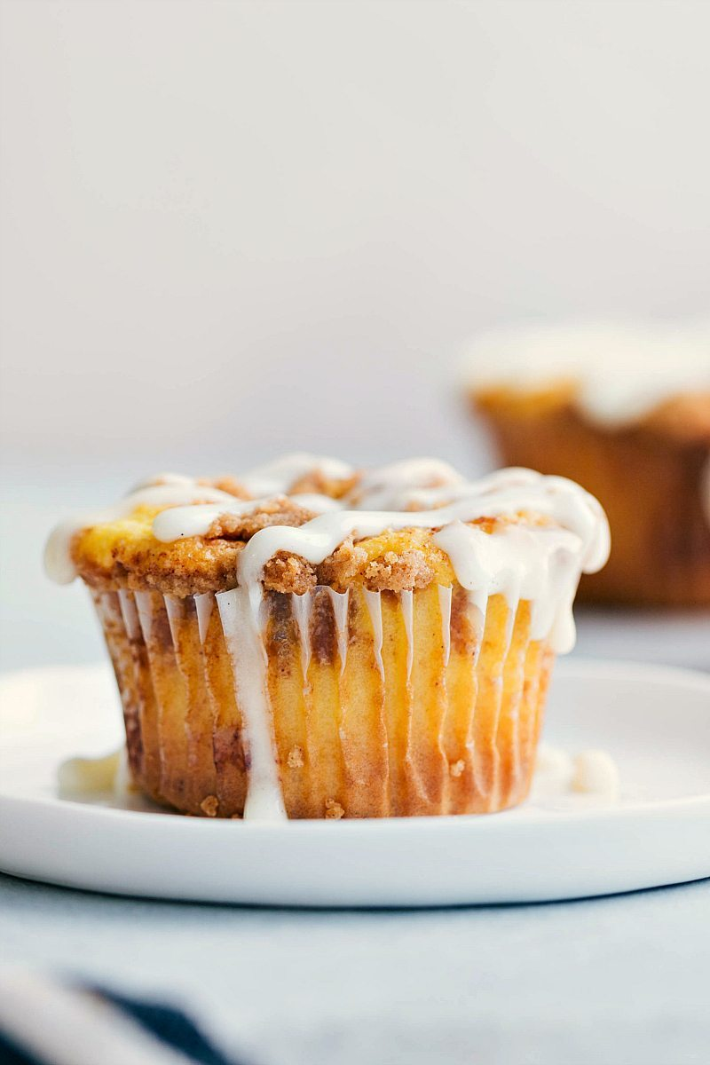 Close-up of one cinnamon roll cupcake on a white plate.