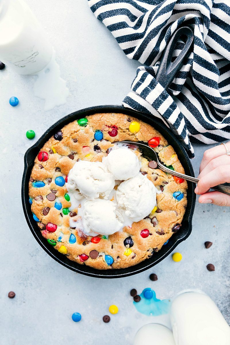 Overhead shot of skillet pizookie with a hand holding a spoon in the dessert