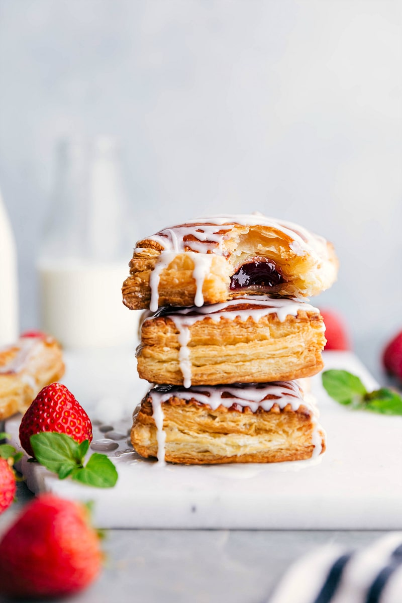 Image of the freshly baked Toaster Strudels stacked on top of each other with a bite out of the top one.