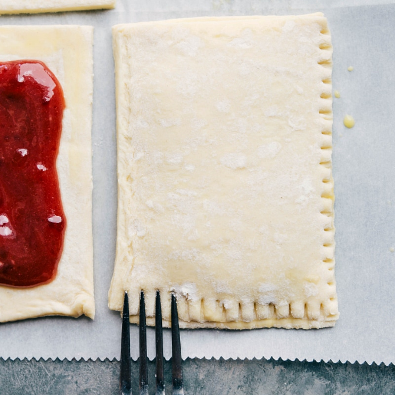 Process shot-- image of the puff pastry layers being sealed with a fork pushing down the edges.