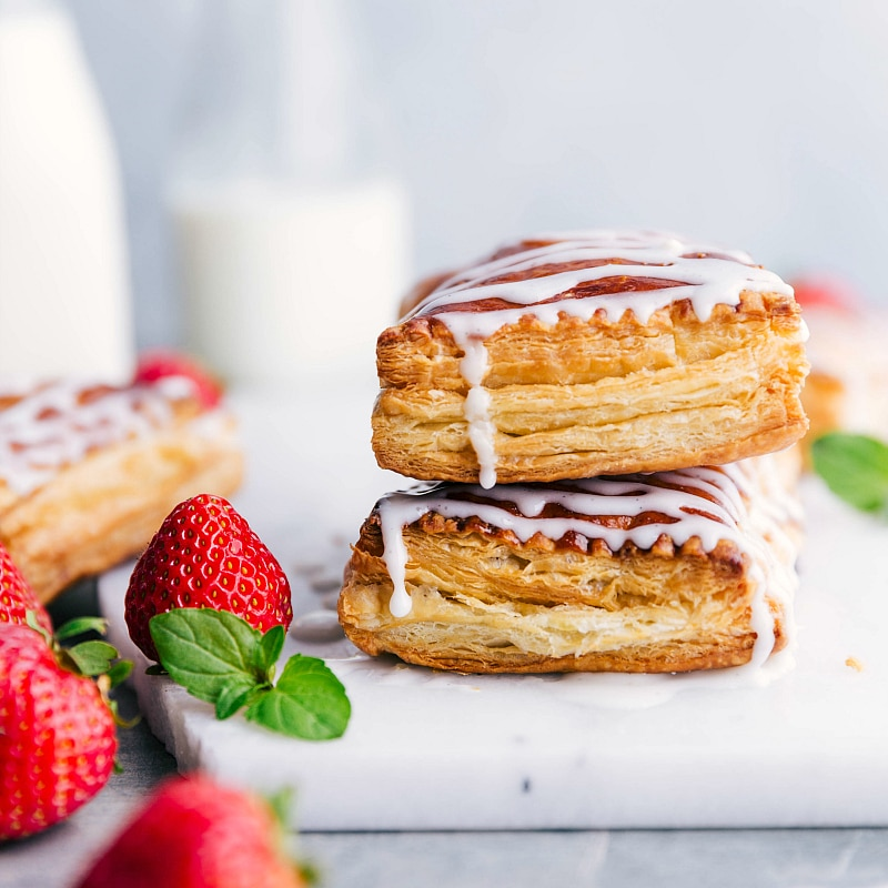 Image of two toaster strudels stacked on top of each other with icing dripping and fresh strawberries