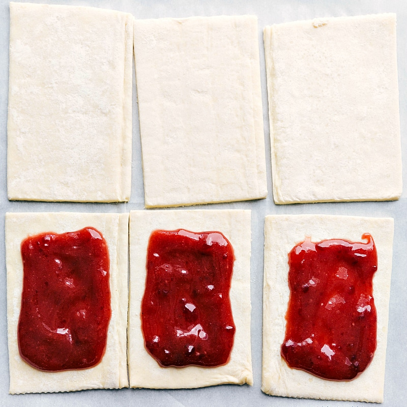 Process shot-- image of the puff pastry pieces with jam added to the center.