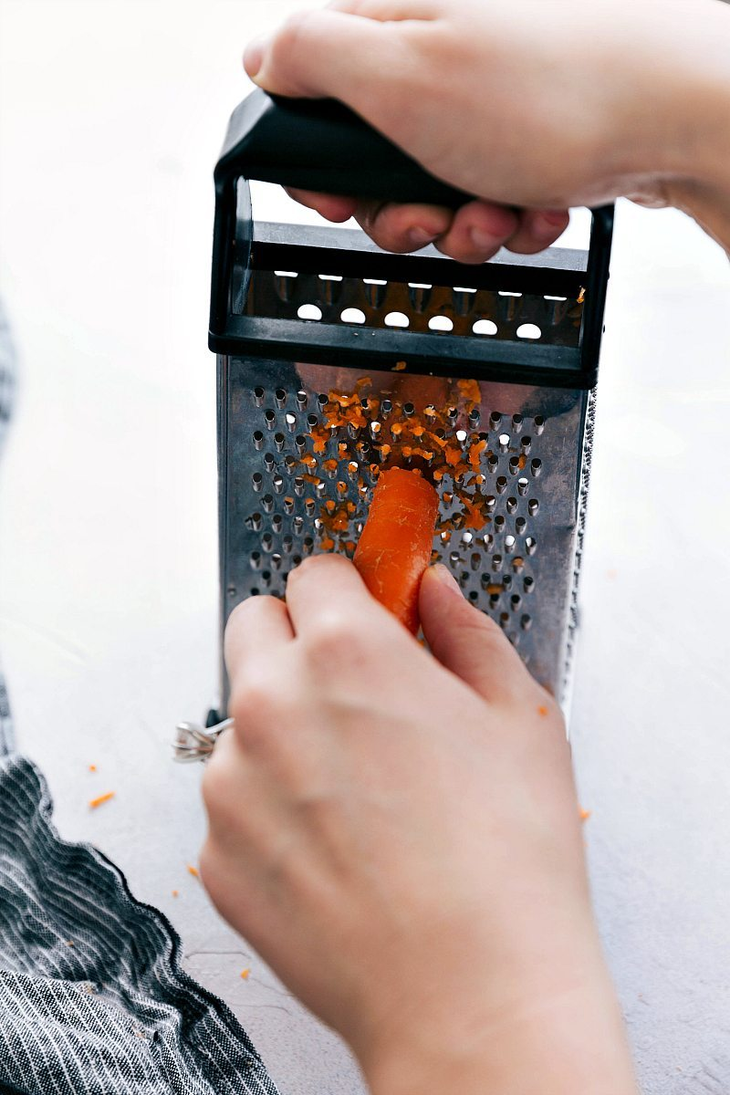 Carrot being grated on fine side of a grater