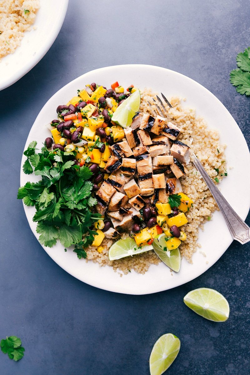 Overhead image of Quinoa chicken bowl with fresh mango salsa and coriander on the side.