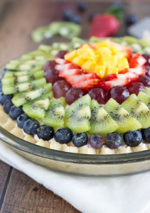 A fresh fruit pie with a sugar cookie crust, a light cheesecake filling, topped with loads of fresh fruit, and lightly glazed with fruit preserves from Chelsea's Messy Apron