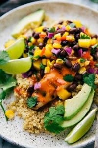 A bed of quinoa with marinated and grilled chicken breast topped with a fresh and healthy mango salsa.