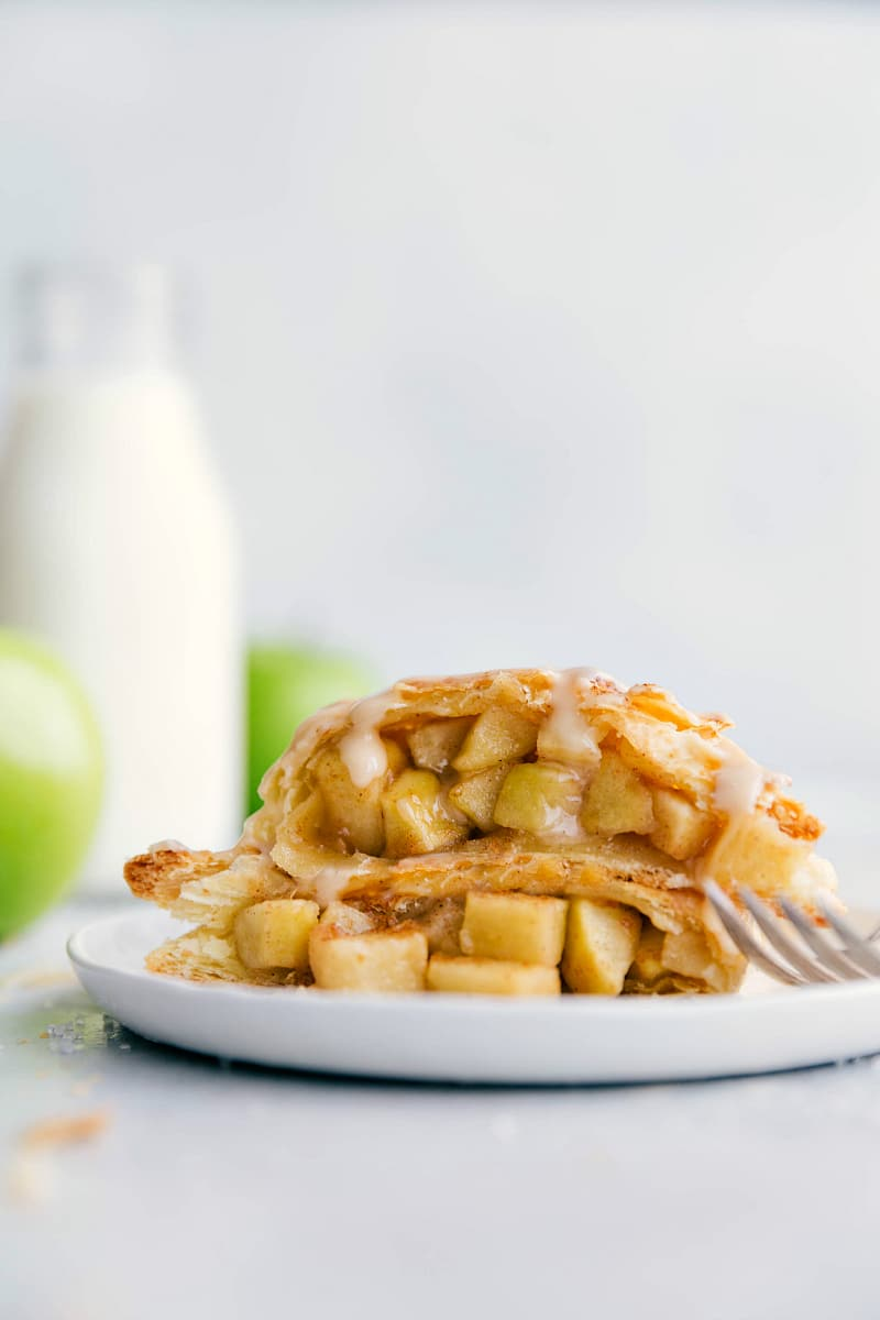 Up close photo of an apple turnover split in half to see the inside packed with sugared apples. Dripping glaze is coming down the apple turnover
