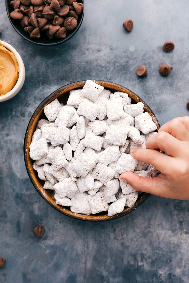 Overhead photo of a bowl filled with Muddy Buddies and a toddler hand grabbing one out.