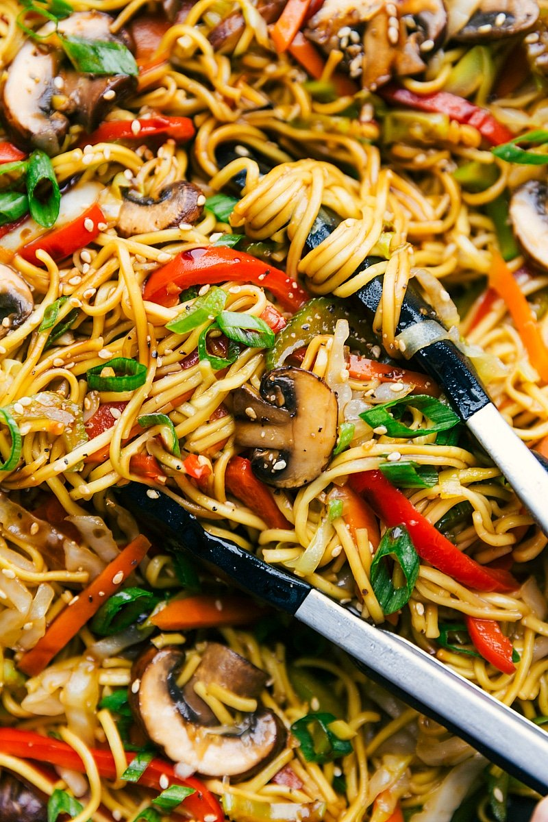 Up close image of the cook chow Mein in a pot with tongs