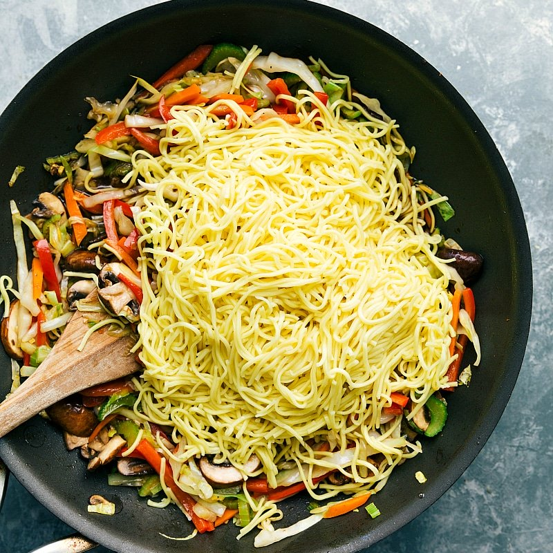 Image of the chow Mein noodles being added to the sauce pan to be mixed in with the veggies