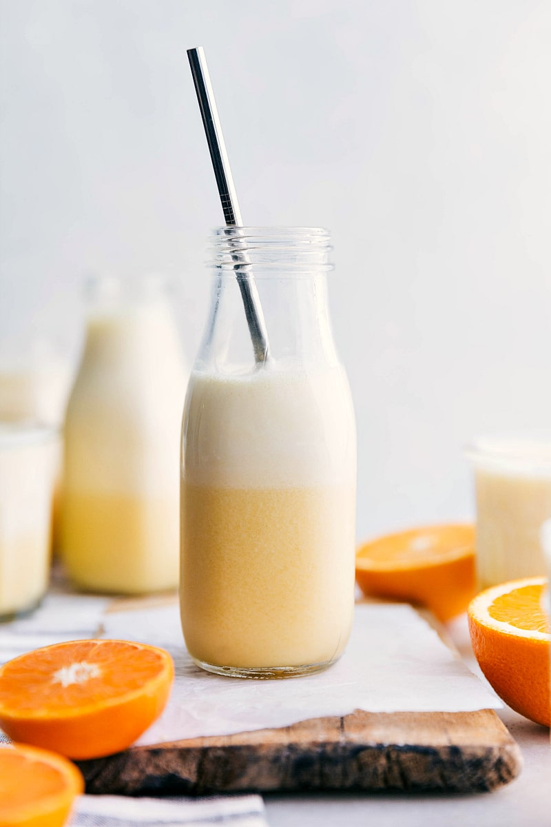 Image of the ready to drink orange Julius with a straw in it and oranges cut out around it