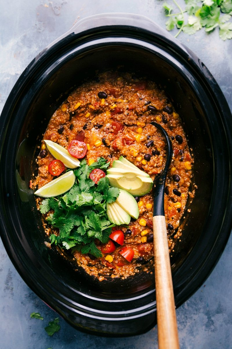 Overhead image of the quinoa enchilada crockpot with a spoon in it and fresh toppings like cilantro, tomatoes, avocado, and limes.