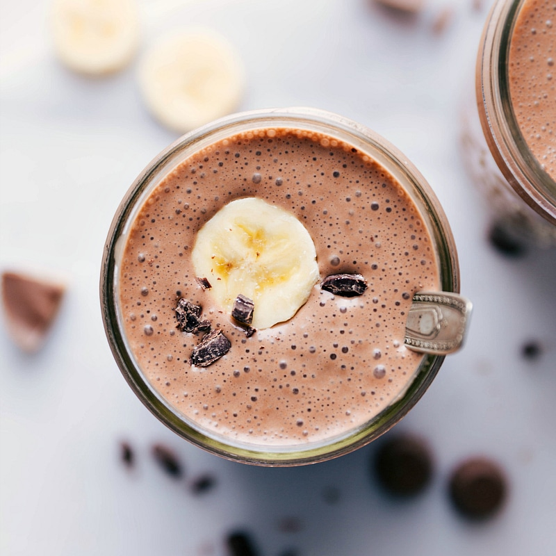 Overhead image of Peanut Butter Protein Shake showing the shake with a banana slice and chocolate chips on top with a spoon.
