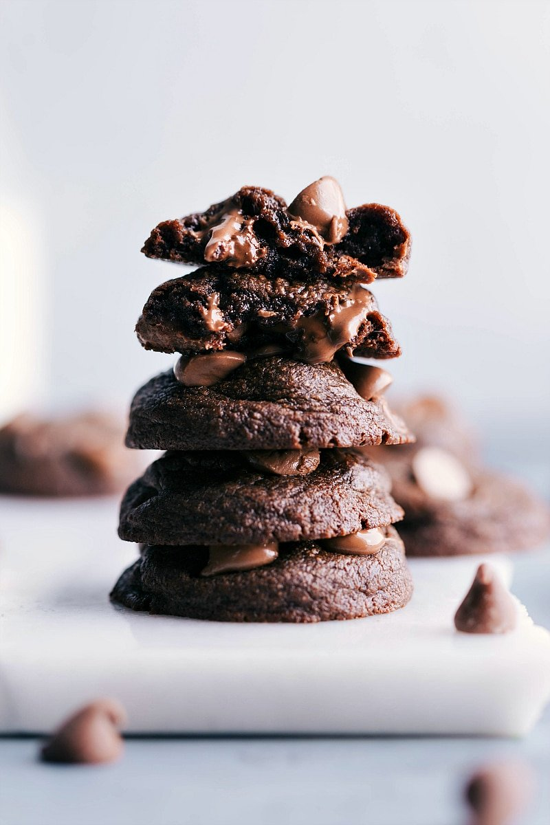 Image of Fudge Brownie Cookies stacked on top of each other with one split in half showing the inside