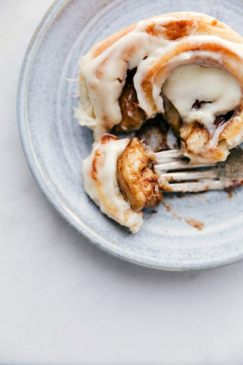 Up close photo of a homemade cinnamon roll with bite taken out of it