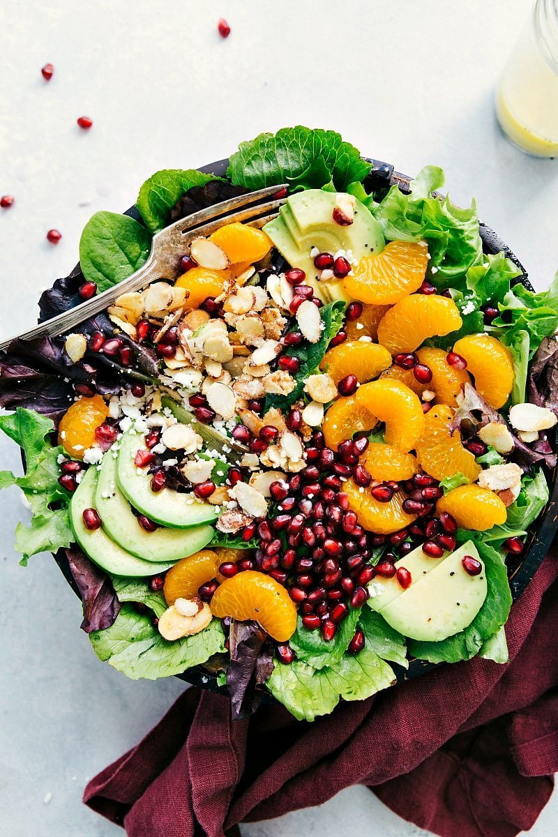 Pomegranate Orange Salad! This delicious winter pomegranate orange salad is topped with mandarin oranges, pomegranate arils, candied almonds, sliced avocado, and feta cheese. chelseasmessyapron.com