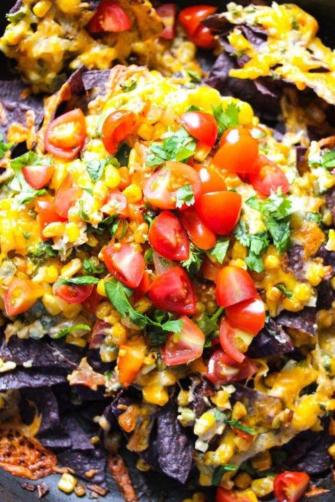 Up close photo of jalapeno nachos with fresh garnishes on top