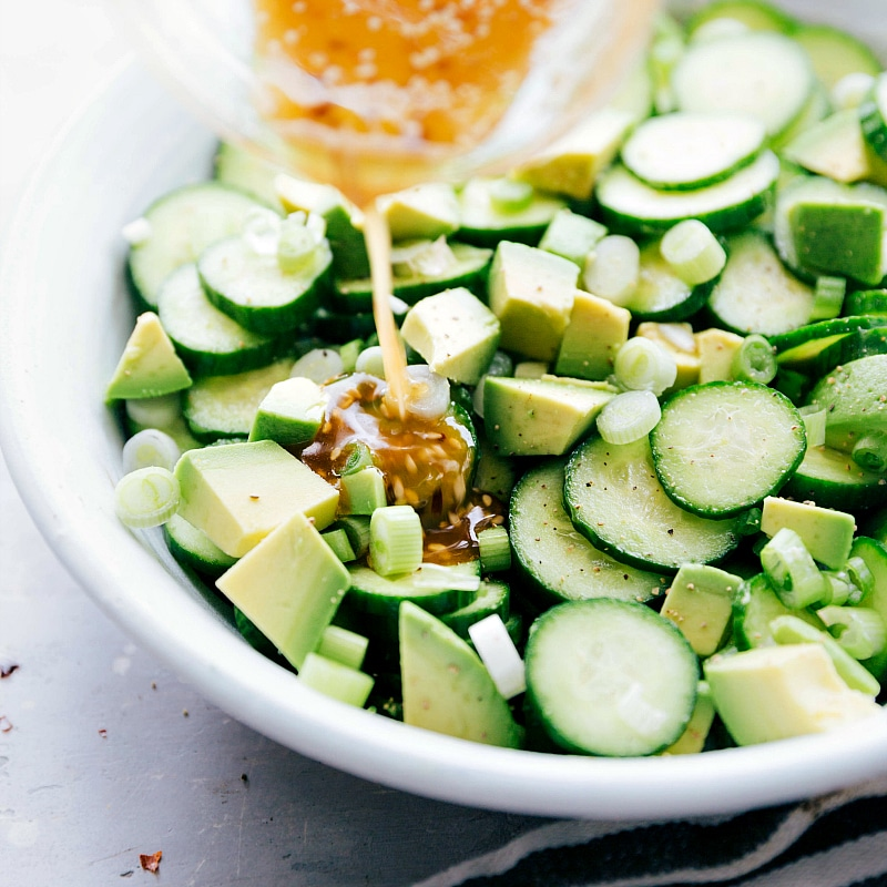 Image of the dressing being added to the asian cucumber salad recipe