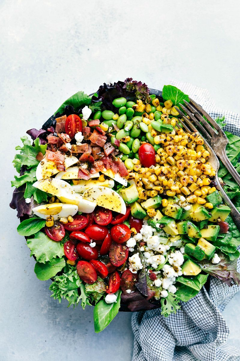 Up close photo of bowl of cobb salad including goat cheese, tomatoes, avocado, hard-boiled eggs, crispy bacon, edamame, and roasted corn