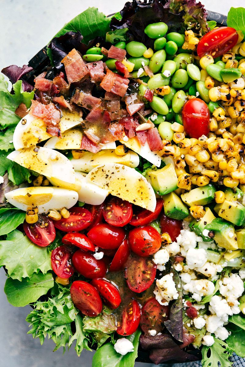 Up close photo of left side of bowl of cobb salad including goat cheese, tomatoes, avocado, hard-boiled eggs, crispy bacon, edamame, and roasted corn