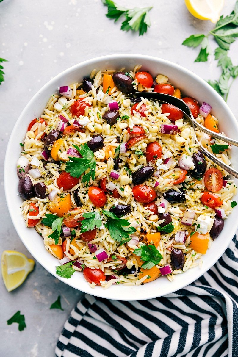 Overhead image of the ready to eat orzo pasta salad in a bowl with spoons in it