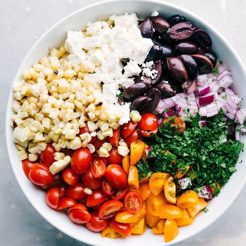 Process shot-- overhead image of all the salad ingredients in a bowl ready to be mixed for this orzo pasta salad
