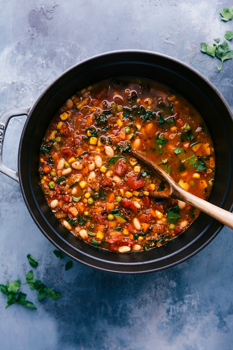 Overhead image of the pot of Healthy Minestrone Soup with a big wooden spoon in it.