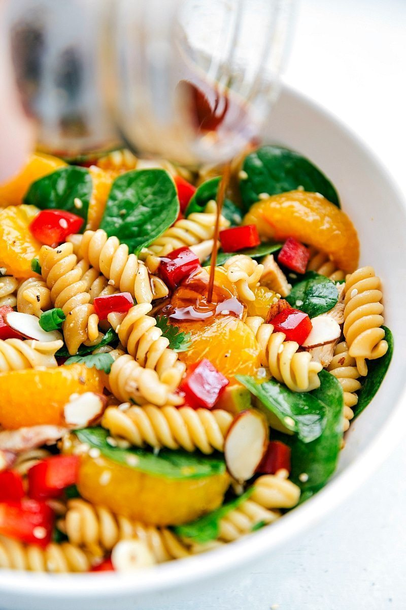 BEST ASIAN PASTA SALAD!! Pasta is tossed with spinach, mandarin oranges, lots of veggies, sliced almonds, chicken and drizzled with a flavorful dressing. via chelseasmessyapron.com