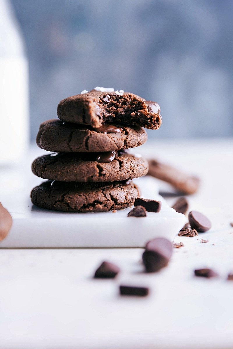 Image of the healthy chocolate cookies stacked on top of each other with a bite out of one of them