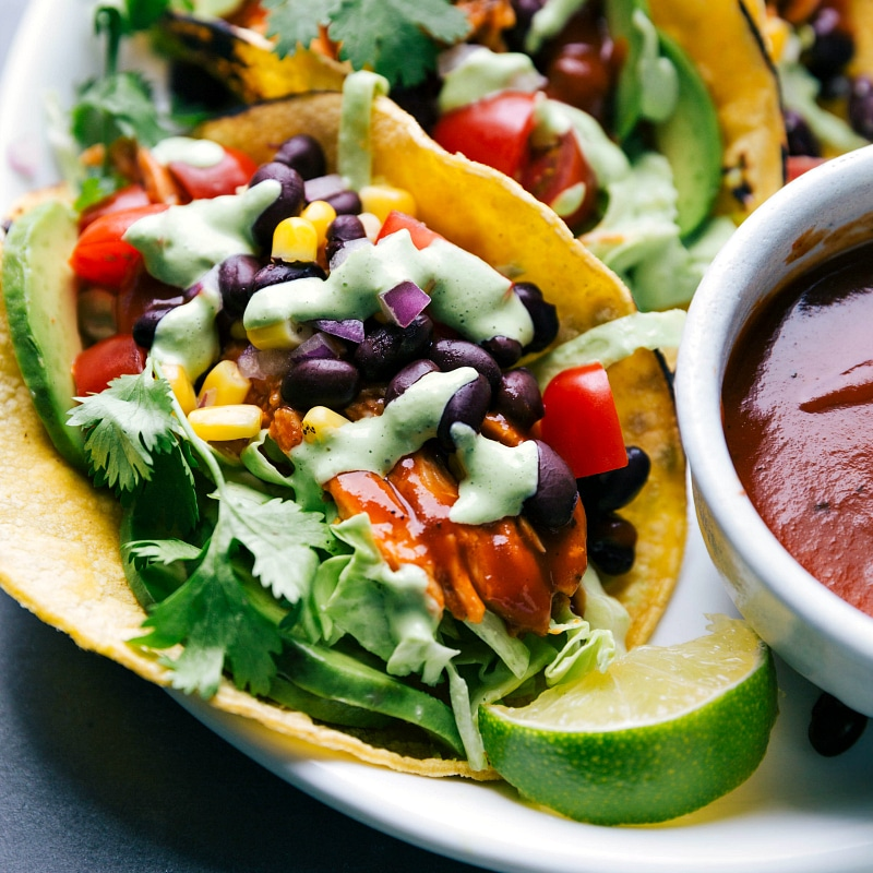 Close-up view of BBQ Chicken Tacos, with a bowl of barbecue sauce nearby.