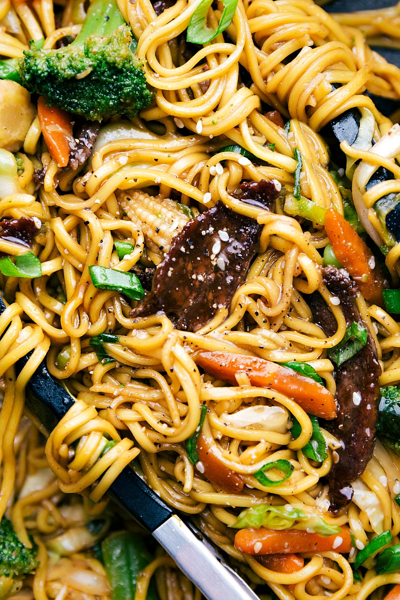Up close shot of finished beef chow mein with tongs holding the noodles