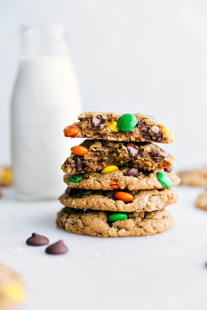 Image of Flourless Monster Cookies stacked on top of each other with one broken in half showing off the middle/