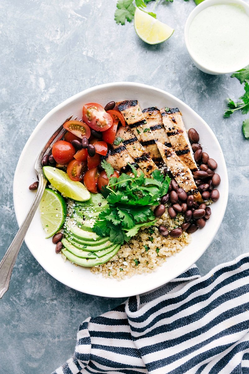 Overhead image of the honey lime chicken in a bowl with quinoa, tomatoes, avocados, and black beans