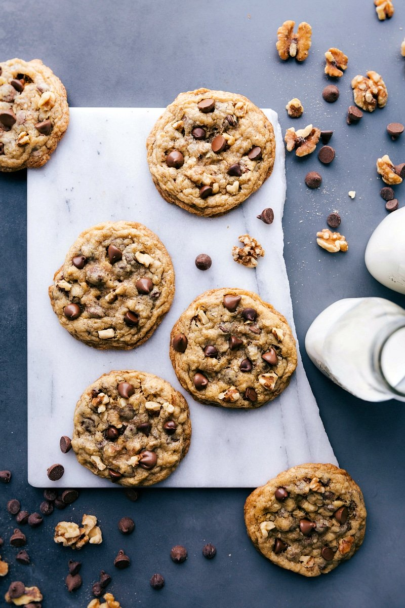 Overhead view of baked DoubleTree Cookies with milk, walnuts and chocolate chips nearby.