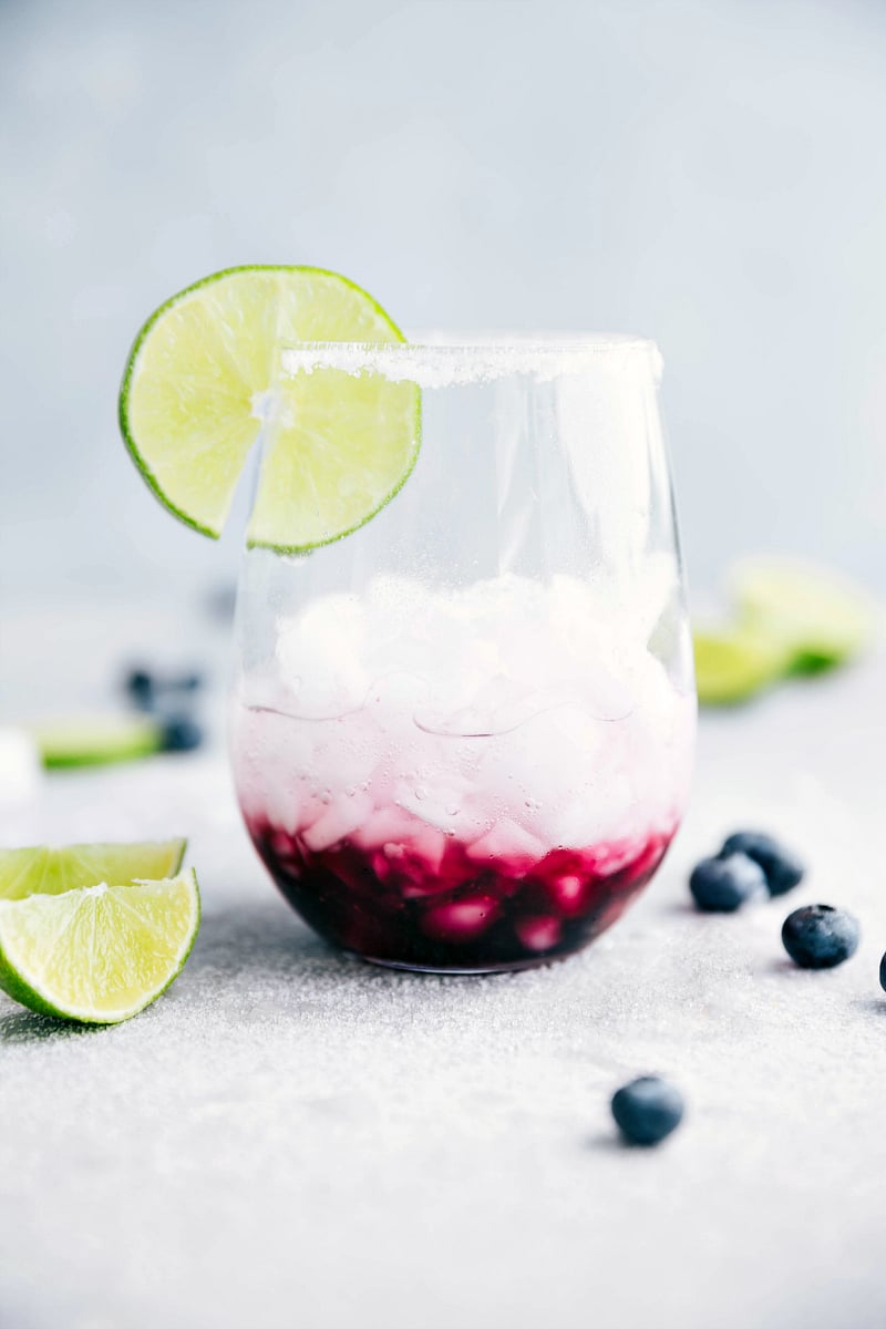 A delicious blueberry mandarine-lime beverage. This spritzer is non-alcoholic made with a sugared blueberry base and a mandarine-lime sparkling water. I chelseasmessyapron.com