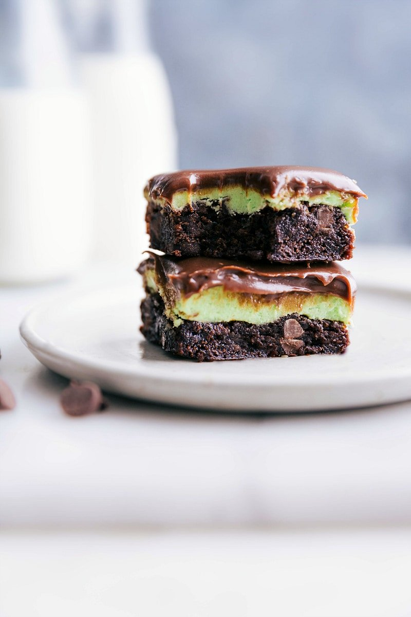 Up-close image of two squares of Mint Brownies stacked on top of each other with a bite taken out of the top one.