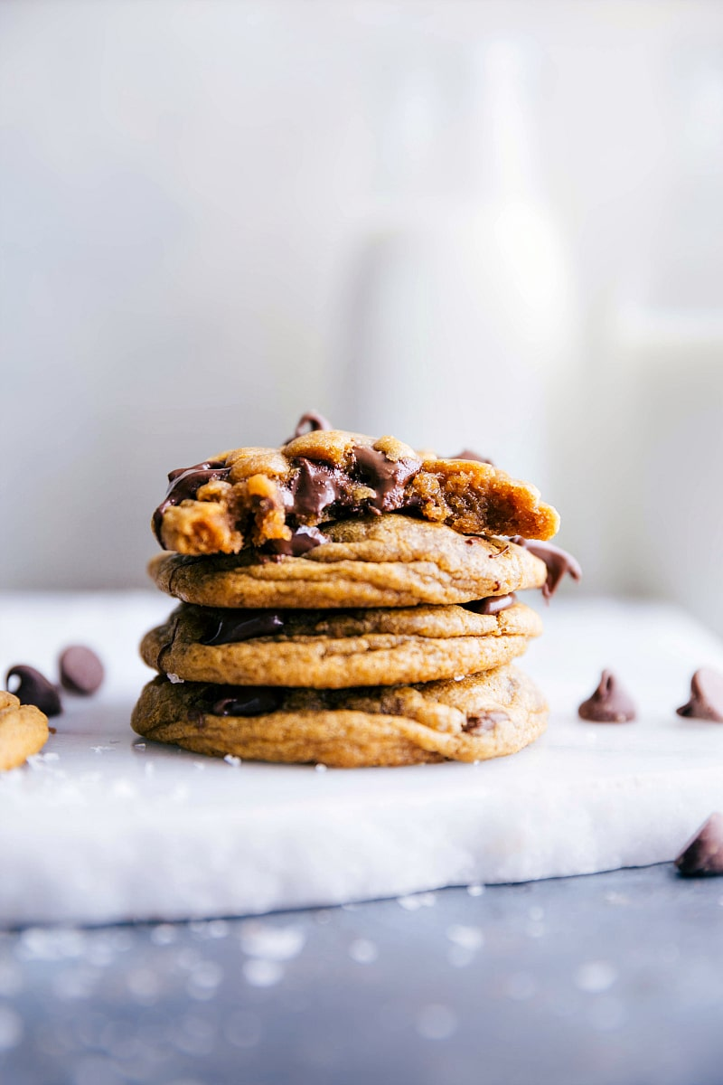 Image of Pumpkin Chocolate Chip Cookies stacked on top of each other with the top one with a bite out of it.