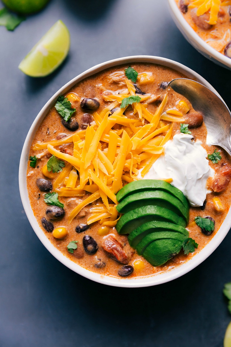 Overhead image of Chicken Chili with shredded cheese, sour cream, and avocado added on top.