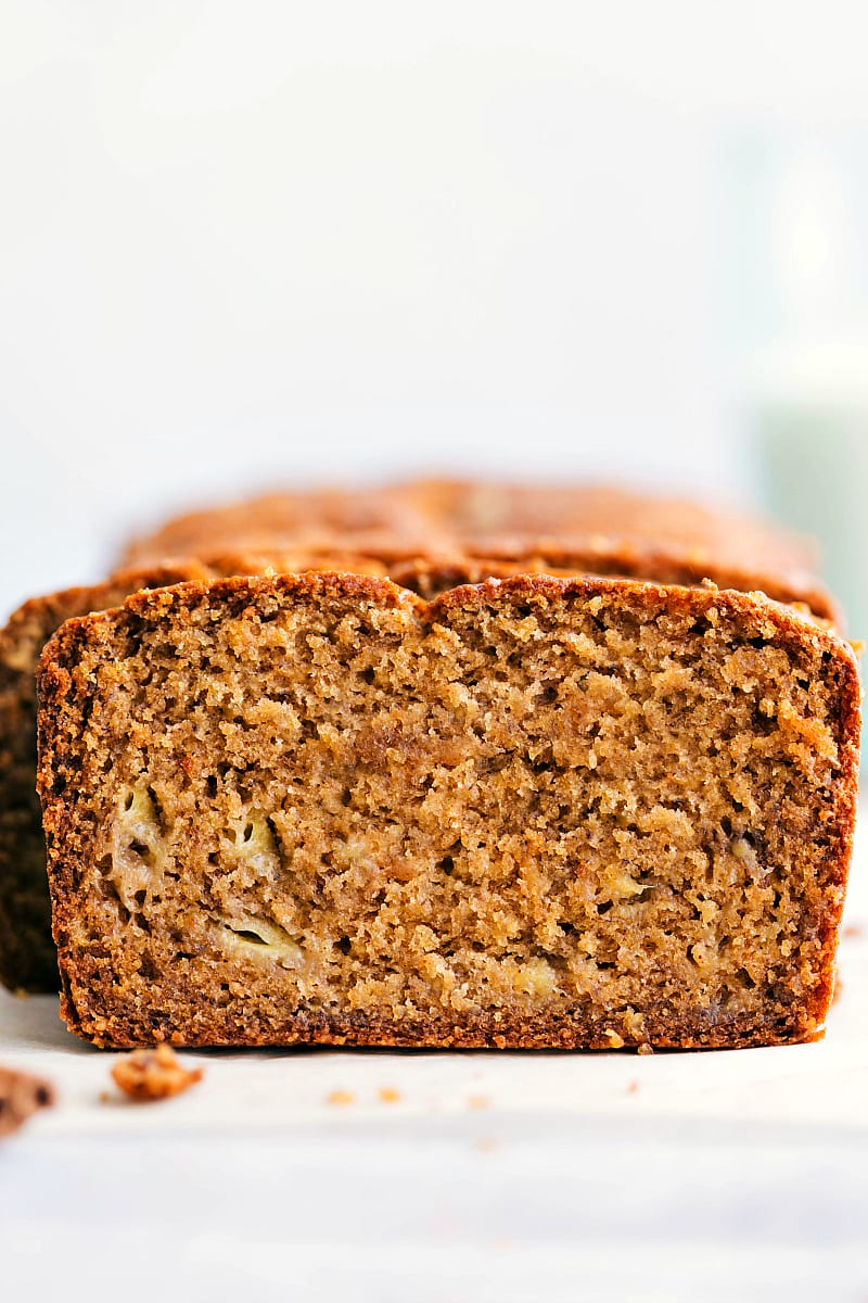 Up-close shot of a slice of this healthy banana bread with the rest of the loaf in the background.