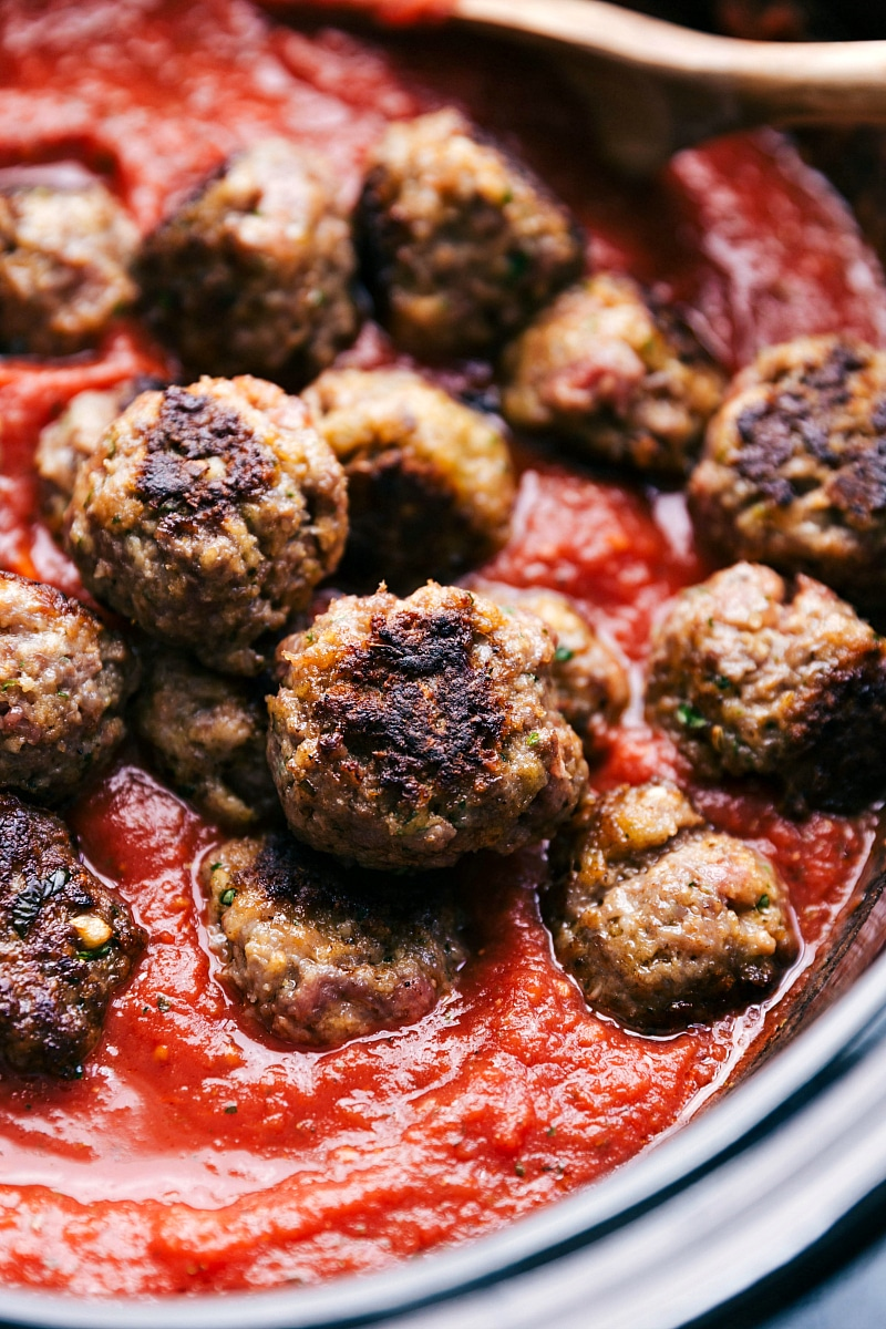 Up close image of the meatballs being put in marinara sauce for this meatball sliders recipe
