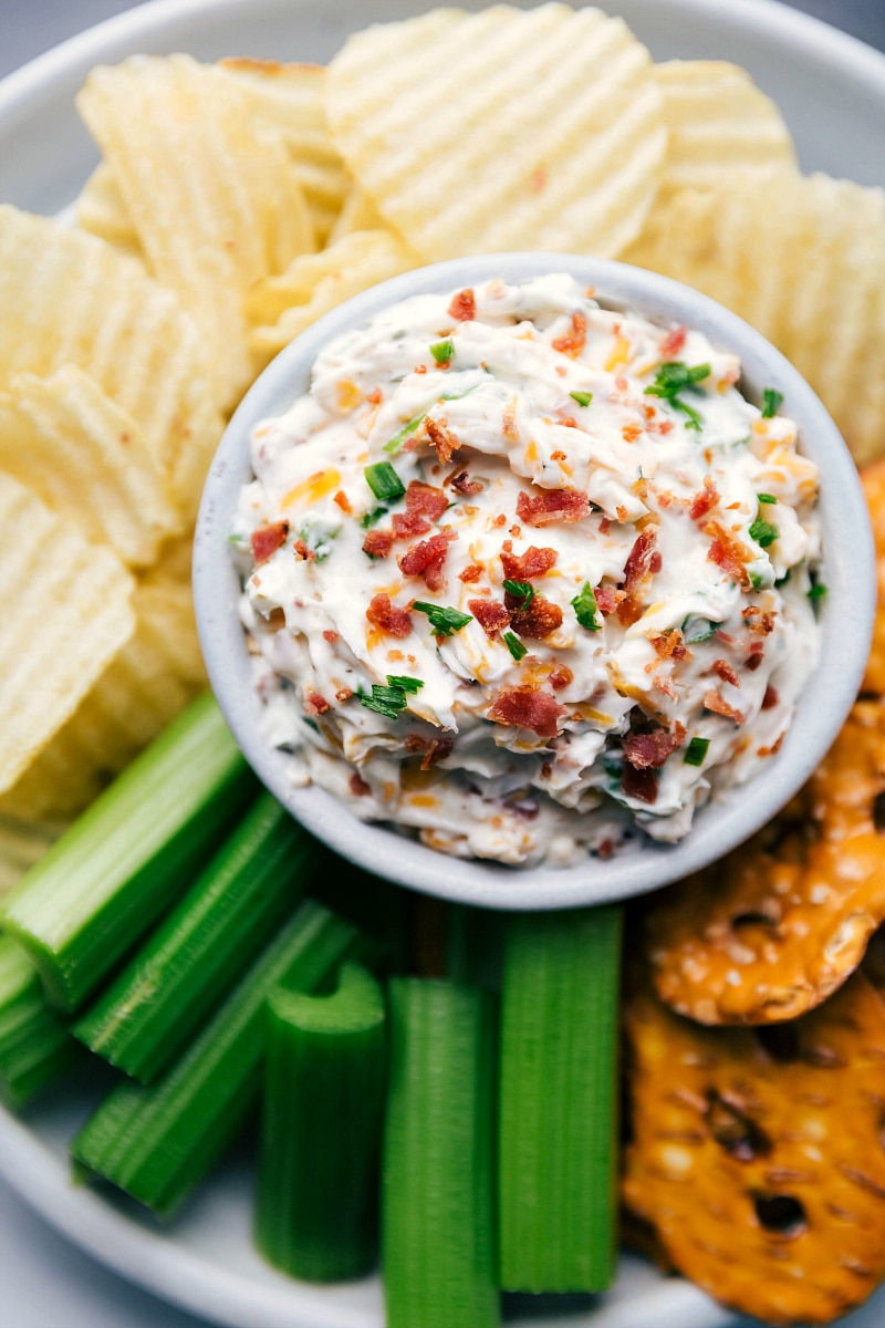 Overhead, close-up view of Baked Potato Dip, surrounded by potato chips and celery sticks.