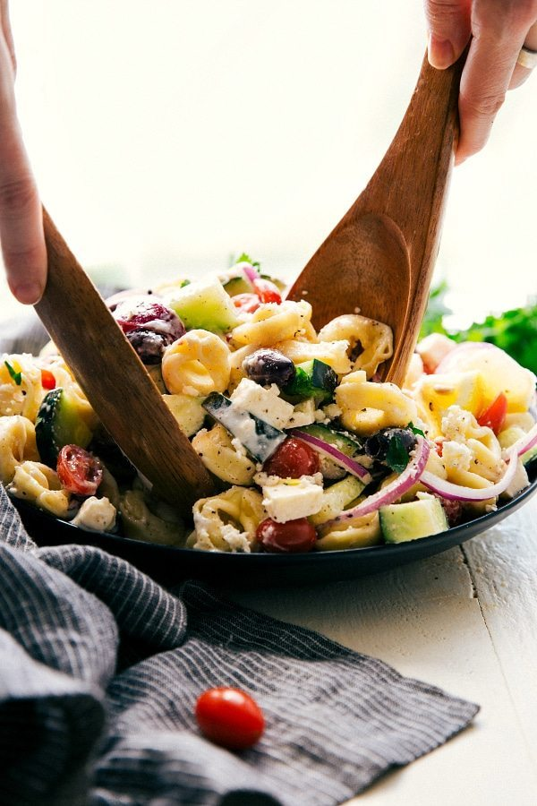 Perfect NO MAYO SALAD for a hot weather BBQ!! Easy Greek tortellini pasta salad with a healthier (no mayo) dressing. Feta, cucumbers, cherry tomatoes, red onions, kalamata olives, and delicious cheese-filled tortellini. Recipe via chelseasmessyapron.com