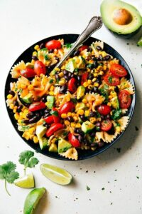A delicious and super simple Tex Mex Pasta Salad with corn, black beans, cherry tomatoes, and avocados. An easy Catalina dressing tops this salad.